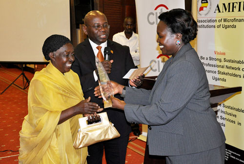 Twinomugisha receiving the Gold award from Hon. Minister of Microfinance