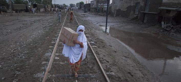 Pakistan flood: A woman carries relief supplies, distributed by the Army